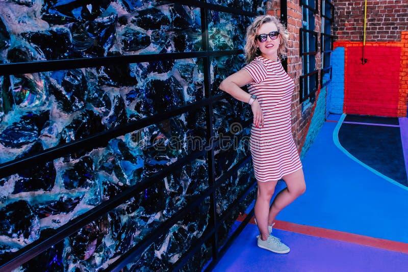 Den unga härliga flickan som poserar på sportlekplatsen i ljusa sportar, gjorde randig klänningen och gymnastikskor arkivfoton