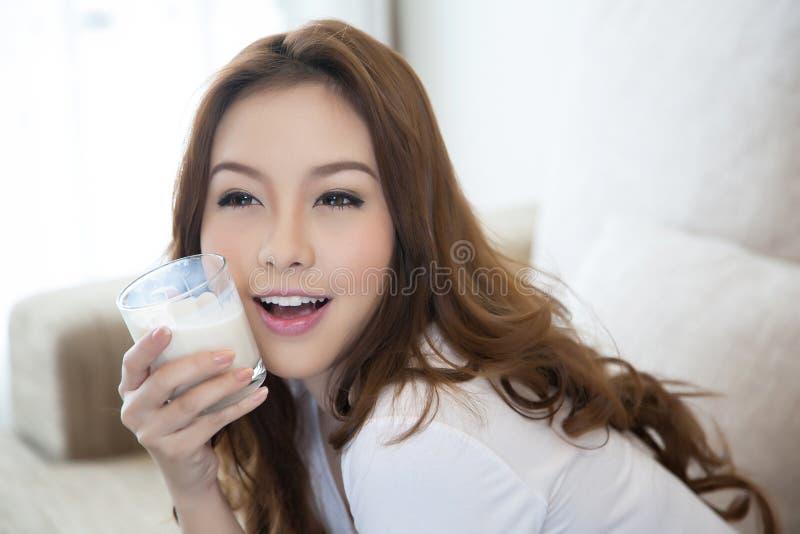 Den unga härliga flickan som rymmer ett exponeringsglas av, mjölkar arkivbilder