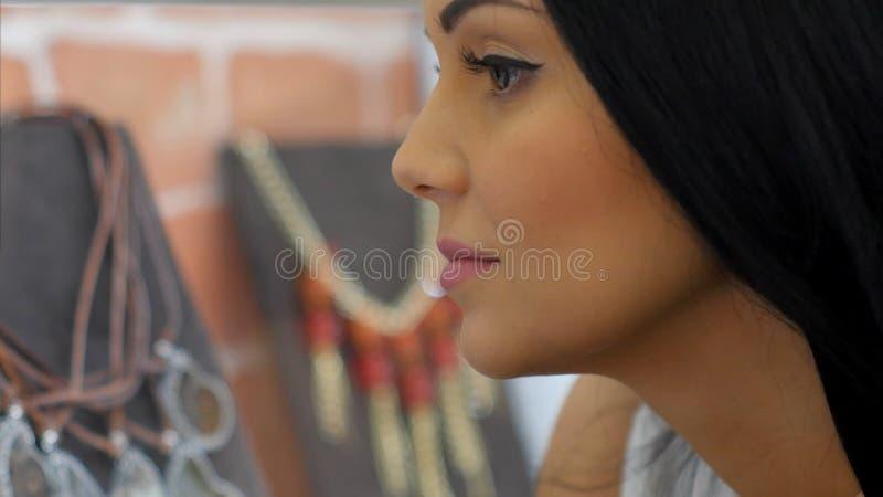 Den unga härliga flickan som ser halsbandet ställer ut på, i smyckenlager arkivbild