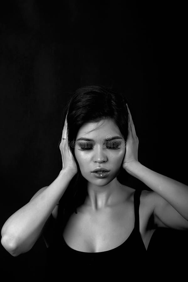 Den unga härliga flickan stänger öronen Hör ingen ondska, svart-vit royaltyfri bild