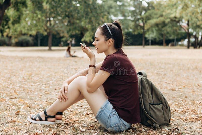 Den unga härliga flickan talar ett stämmakommando in i en mobiltelefon arkivfoton