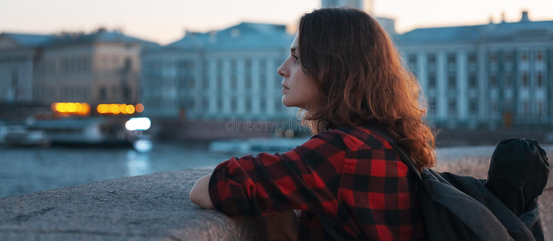 Den unga härliga flickaturisten ser staden på bakgrunden arkivbild