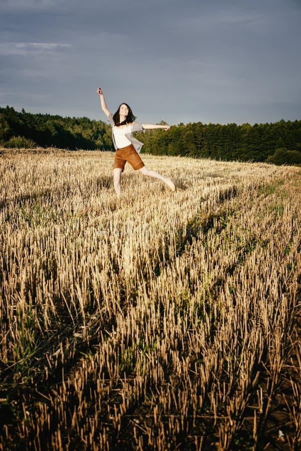 Den unga härliga fria lyckliga kvinnan hoppar lyckligt med leende arkivfoto