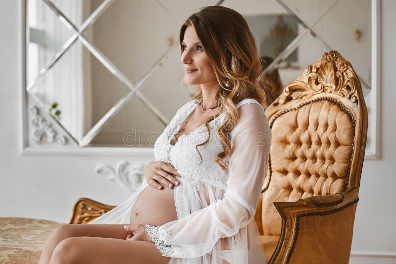 Den unga härliga gravida kvinnan med blont hår och med försiktig makeup i trendig damunderkläder och i peignoir sitter på royaltyfria bilder