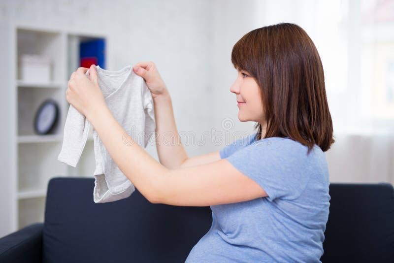 Den unga härliga gravida kvinnan som ser, behandla som ett barn kläder för ` s arkivfoto
