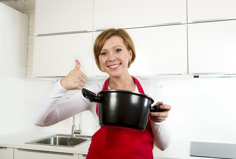 Den unga härliga hem- kockkvinnan i rött förkläde på innehavskeden för inhemskt kök och matlagning lägger in med läcker soppa royaltyfri bild