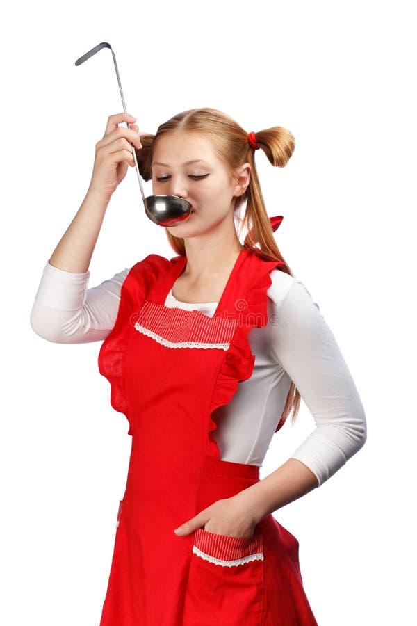 Den unga härliga hemmafrun i rött förkläde med roliga hästsvansar smakar royaltyfri foto