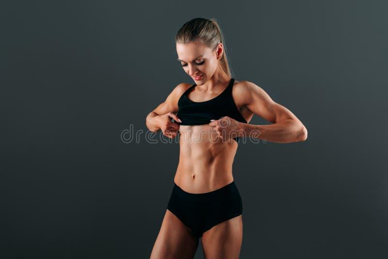 Den unga härliga idrotts- flickan med ett härligt idrotts- diagram visar dess muskler Konditioninstruktören visar hans kropp efte arkivbilder