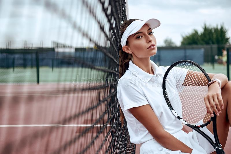 Den unga härliga idrottskvinnan med sammanträde för tennisracket på tennis förtjänar på tennisbanan Sportmode arkivbild