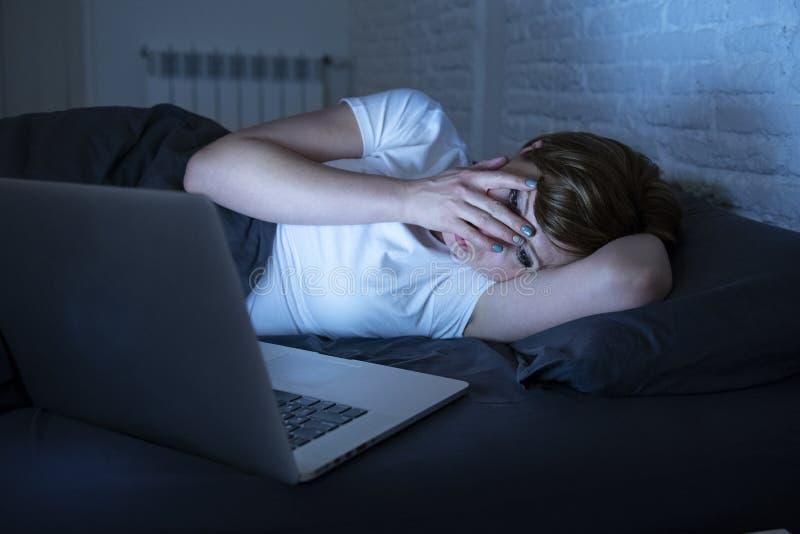 Den unga härliga internet missbrukade den sömnlösa och trötta kvinnan som sent arbetar på bärbara datorn i säng på natten fotografering för bildbyråer