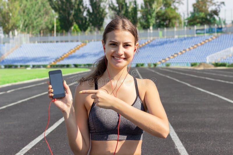 Den unga härliga konditionflickan stting på lyssnande musik för löparbana utomhus och visar på telefonen med hennes finger fit kv arkivbild