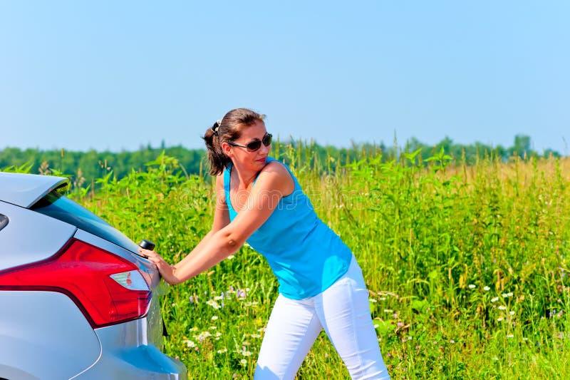 Den unga härliga kvinnan är den driftiga brutna bilen på vägen arkivfoto