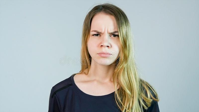 Den unga härliga kvinnan är ilsken på en vit bakgrund ilsket kvinnabarn arkivfoto