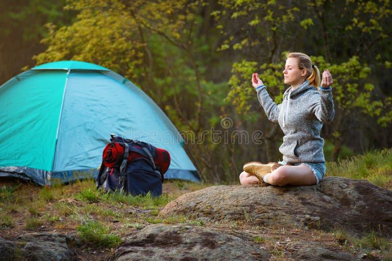 Den unga härliga kvinnan öva yoga i en vandring nära tältet A arkivfoton