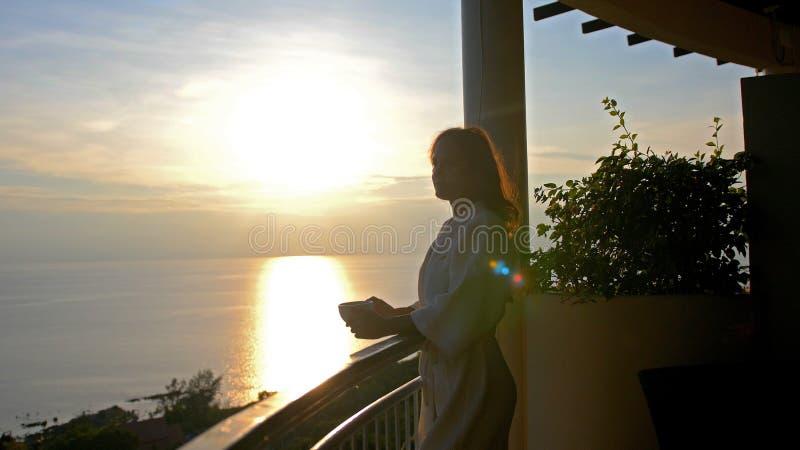 Den unga härliga kvinnan bär badrockdrinkkaffe i morninigen under fantastiska soluppgångställningar på terrassen av henne fotografering för bildbyråer