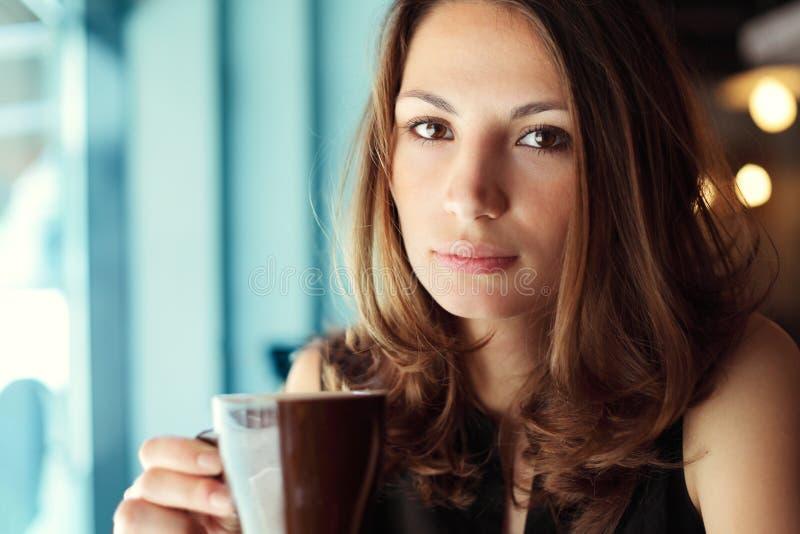Den unga härliga kvinnan dricker kaffe i kafé arkivfoton