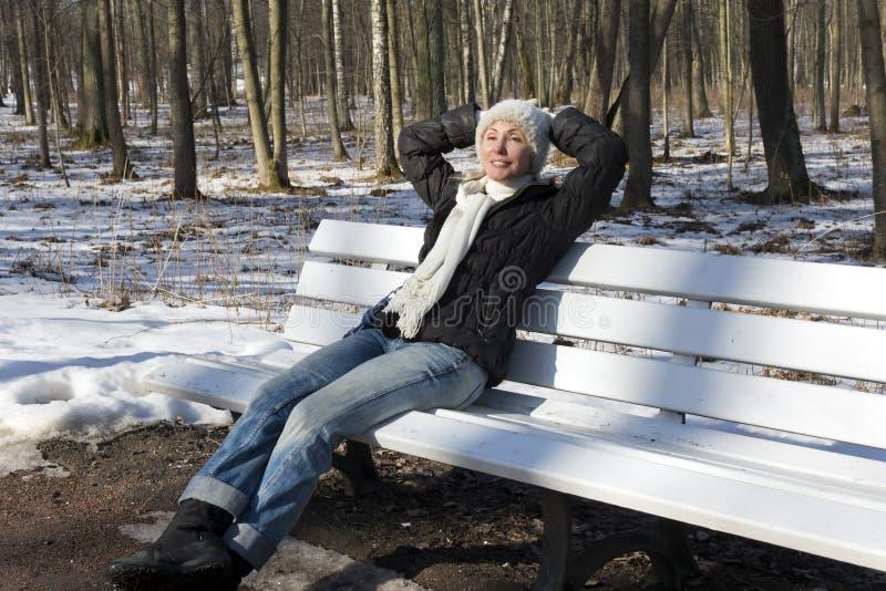 Den unga härliga kvinnan har en vila på en bänk i vintern att parkera fotografering för bildbyråer