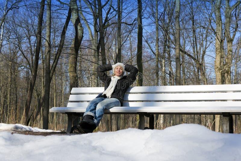 Den unga härliga kvinnan har en vila på en bänk i vintern att parkera arkivbilder