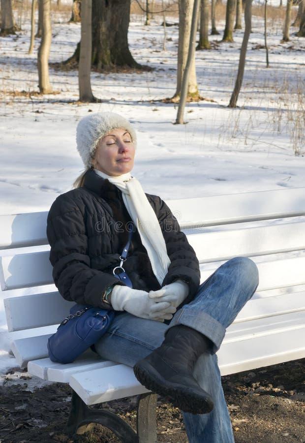 Den unga härliga kvinnan har en vila på en bänk i vintern att parkera arkivfoton