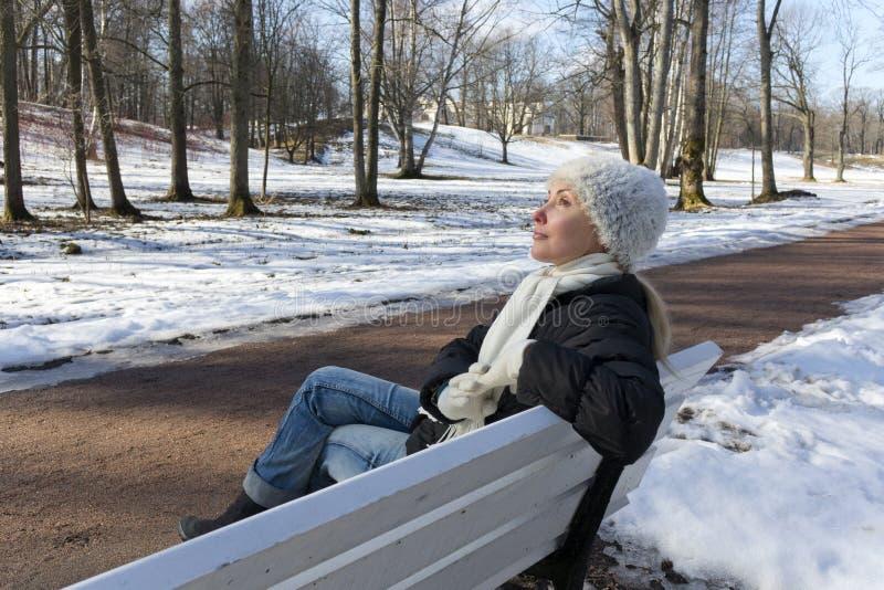 Den unga härliga kvinnan har en vila på en bänk i vintern att parkera royaltyfria bilder