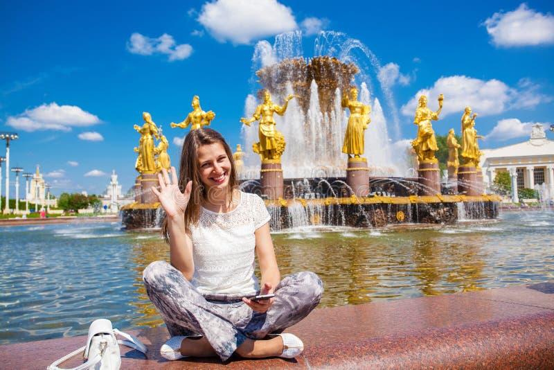 Den unga härliga kvinnan har ett vilasammanträde nära springbrunnen royaltyfri fotografi