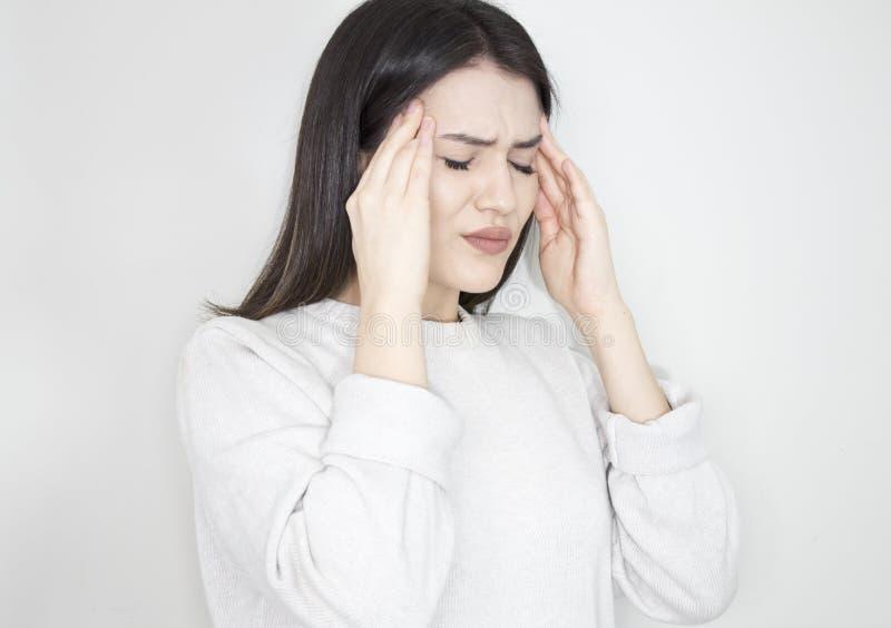 Den unga härliga kvinnan har huvudvärk, på grå bakgrund arkivfoto