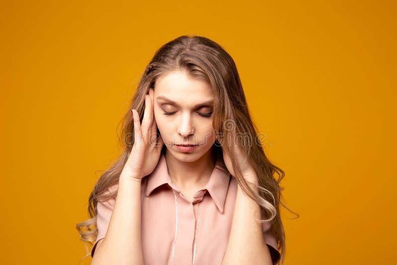 Den unga härliga kvinnan har huvudvärken som isoleras på grå bakgrund royaltyfri bild