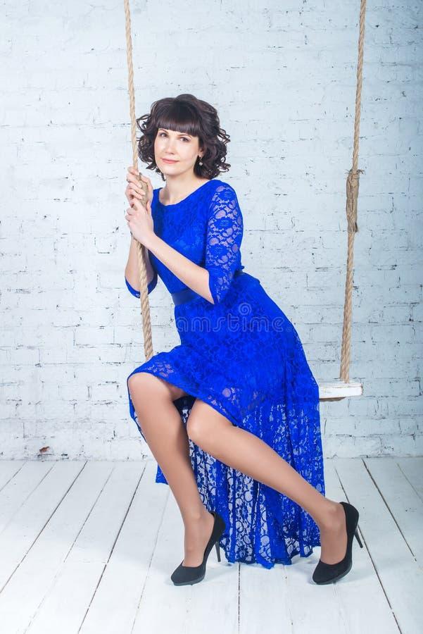 Den unga härliga kvinnan i blått klär sammanträde på gungabakgrund av den vita tegelstenväggen royaltyfria bilder