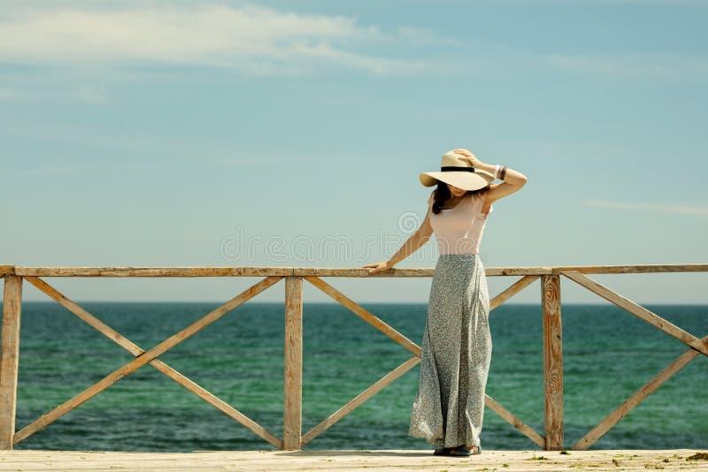 Den unga härliga kvinnan i en lång kjol och hatt står på ett trä royaltyfria foton