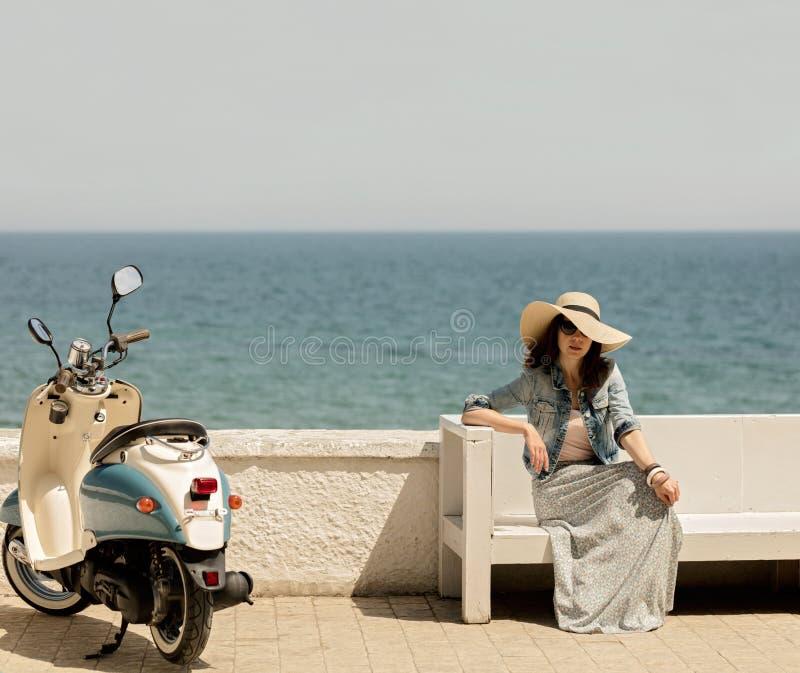 Den unga härliga kvinnan i en lång kjol sitter på en bänk på stranden royaltyfri foto