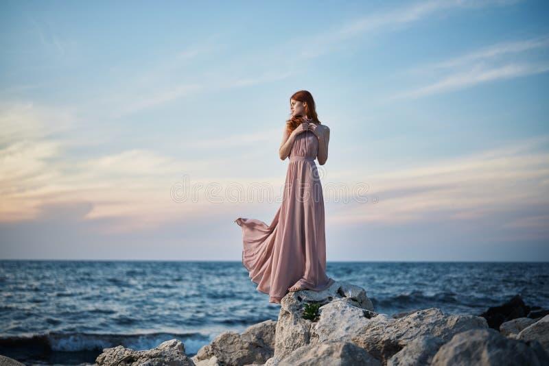 Den unga härliga kvinnan i en lång rosa färgklänning står på stenar på kusten royaltyfria bilder