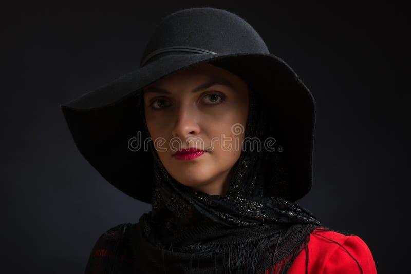 Den unga härliga kvinnan i en svart hatt med sned bollfält, en openwork halsduk och den röda klänningen royaltyfri fotografi