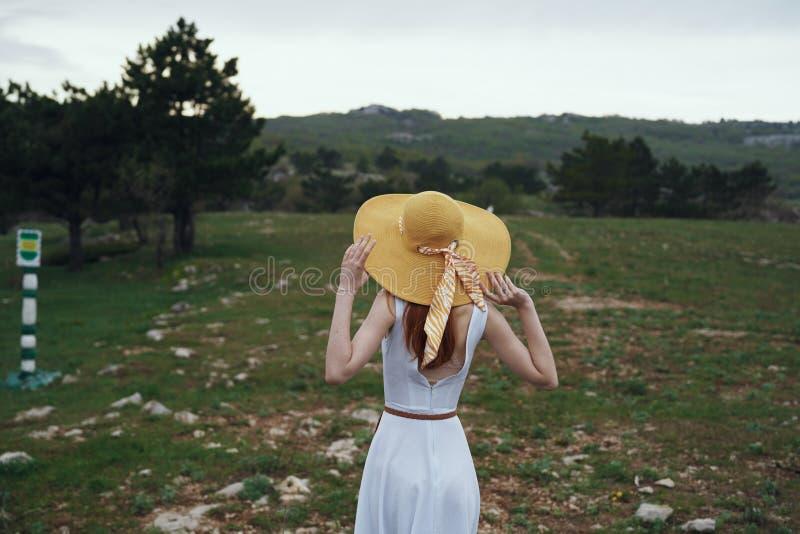 Den unga härliga kvinnan i en vit klänning och hatt går i bergen arkivbilder