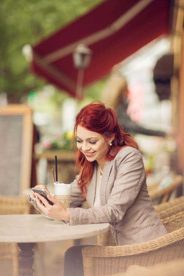 Den unga härliga kvinnan i ett gatakafé som tycker om ett kaffe, är upptagen med hennes mobiltelefon arkivfoton