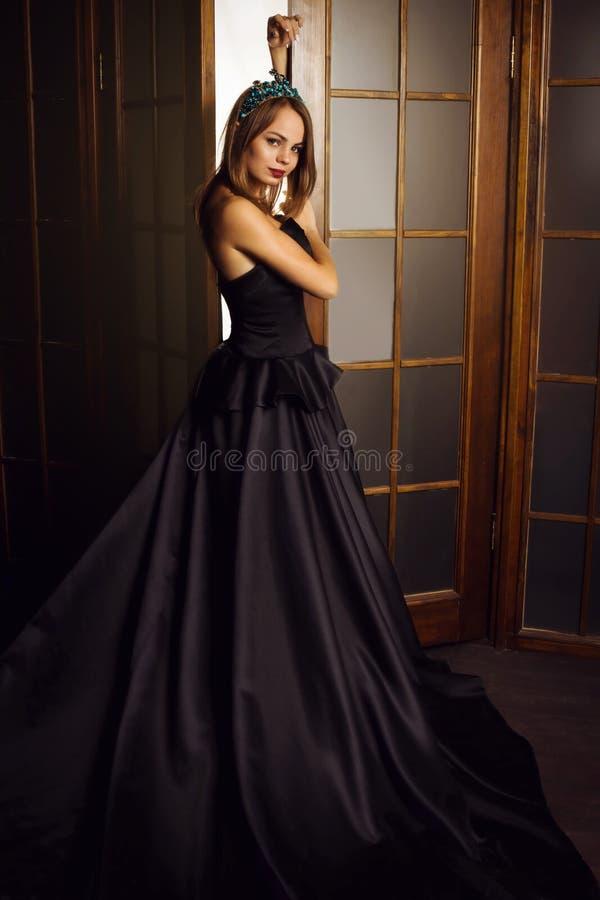 Den unga härliga kvinnan i lång svart klänning och diamanten krönar royaltyfri foto