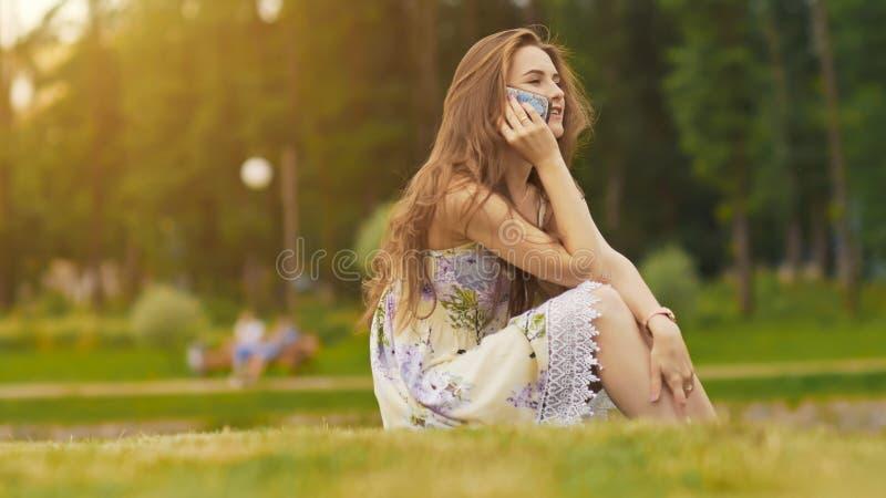Den unga härliga kvinnan i sommarklänning med långt hårsammanträde på gräs i gräsplan parkerar och tala på telefonen som ler arkivbild
