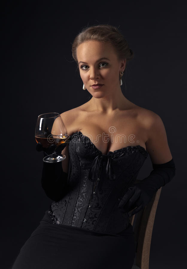 Den unga härliga kvinnan i svart korsetterar med exponeringsglas av konjak royaltyfri bild