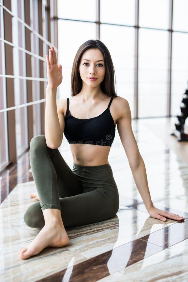 Den unga härliga kvinnan kopplar av, innan han gör yoga i yogastudio Sporthälsobegrepp arkivbilder