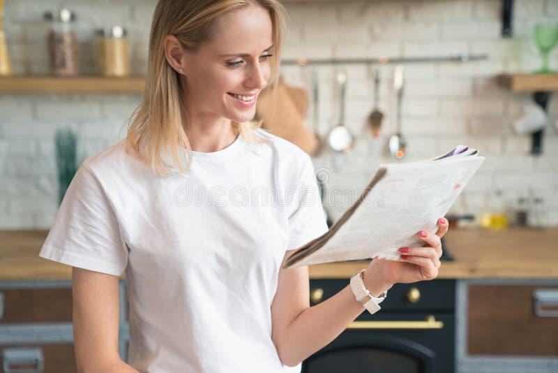 Den unga härliga kvinnan läser hennes morgonpress och ler, medan ha frukosten i köket B?rande vit skjorta arkivbilder