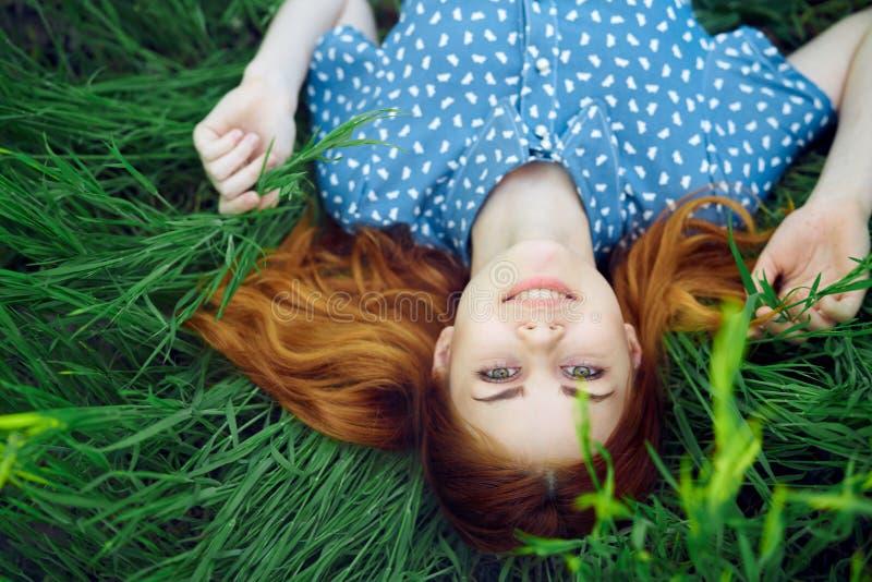 Den unga härliga kvinnan ligger i gräset i fältet, sommar arkivfoton