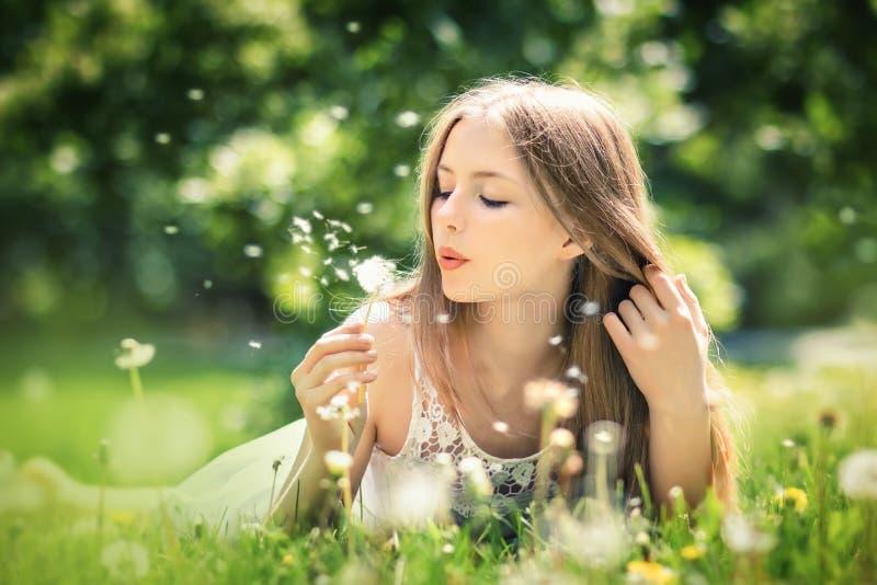 Den unga härliga kvinnan ligger på ett gräs royaltyfri fotografi