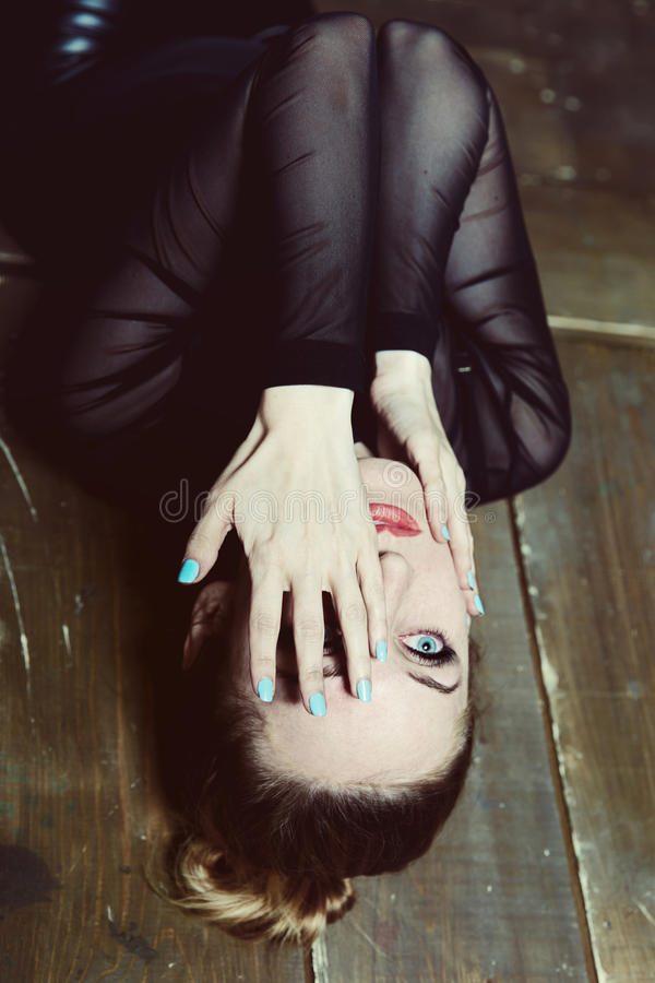 Den unga härliga kvinnan ligger på golvet royaltyfria foton