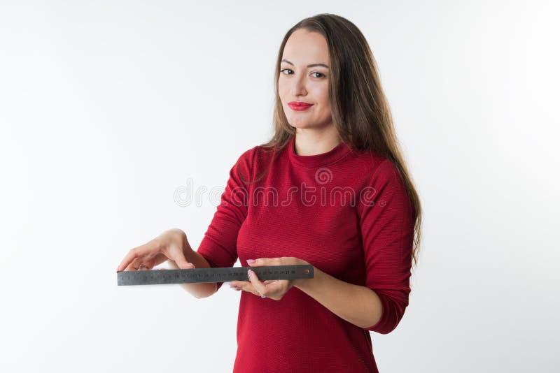 Den unga härliga kvinnan mäter något med linjalen arkivbilder