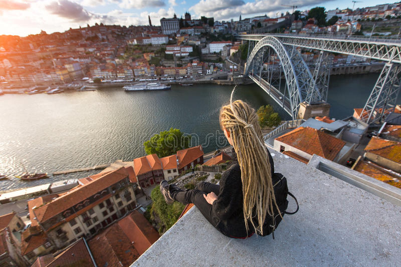 Den unga härliga kvinnan med blonda dreadlocks möter solnedgång på visningplattformen mitt emot den Dom Luis I bron över floden fotografering för bildbyråer