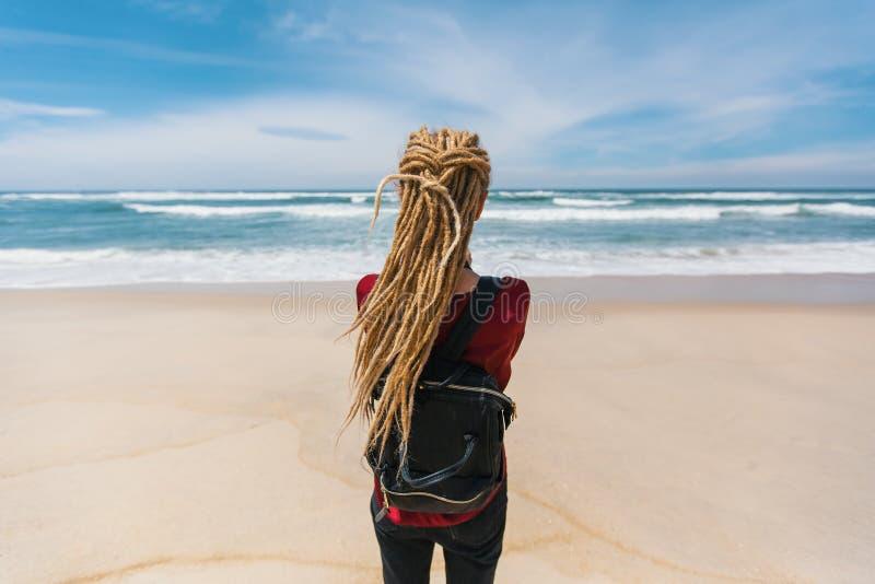 Den unga härliga kvinnan med blonda dreadlocks ser havet arkivfoton