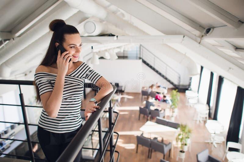 Den unga härliga kvinnan med brunt hår ser åt sidan, medan tala på en smartphone En kvinnlig student för charmig brunett arkivbild