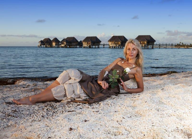 Den unga härliga kvinnan med en ros sitter på sand på havskanten arkivbild