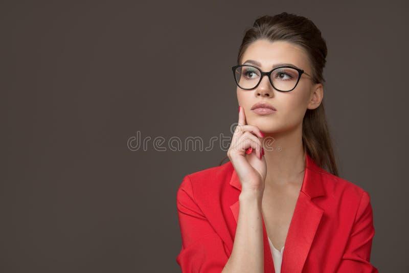 Den unga härliga kvinnan med exponeringsglas ser upp hänsynsfullt Rymma en hand nära hennes framsida Gr? f?rgbakgrund arkivbilder