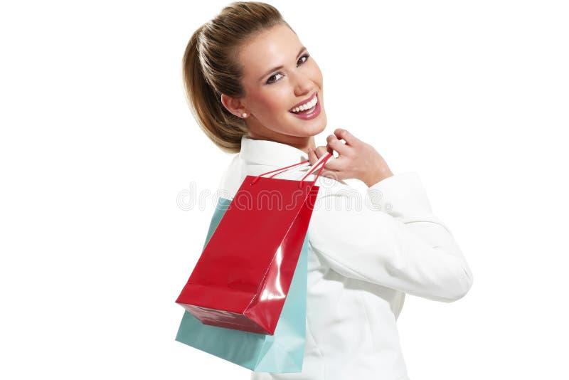 Den unga härliga kvinnan med shopping hänger lös arkivfoton