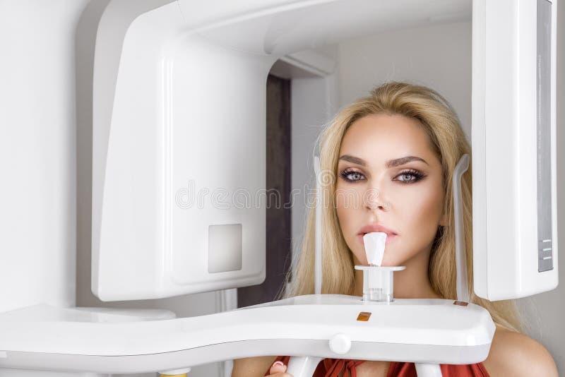 Den unga härliga kvinnan med härliga vita tänder är på tandläkaren royaltyfria bilder